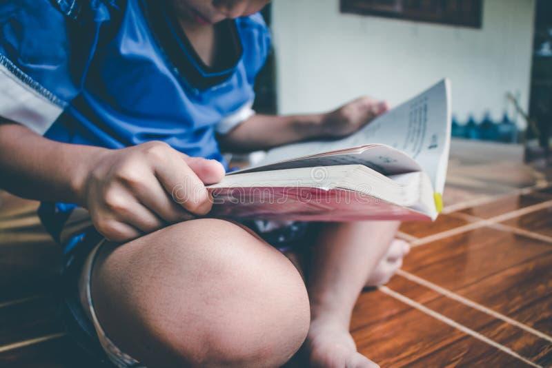 El muchacho est? leyendo el libro para preparar el examen el este lunes que viene imagen de archivo