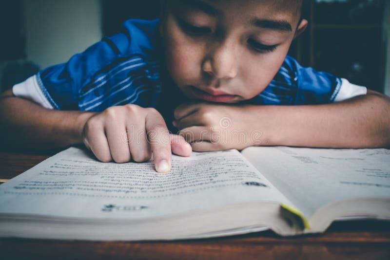 El muchacho est? leyendo el libro para preparar el examen el este lunes que viene imagen de archivo libre de regalías