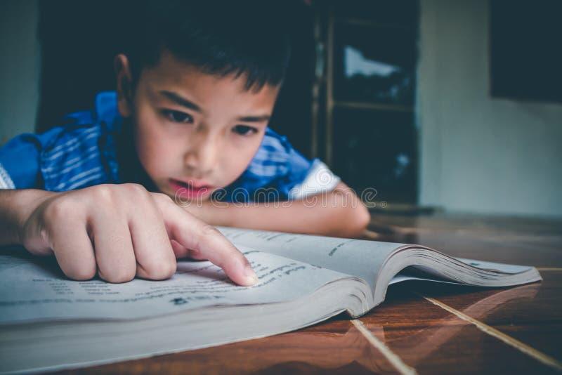El muchacho est? leyendo el libro para preparar el examen el este lunes que viene imagenes de archivo