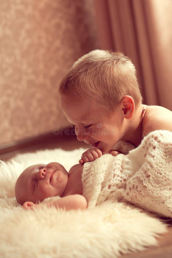 El muchacho europeo blanco 5 años comunica con su hermano recién nacido foto de archivo