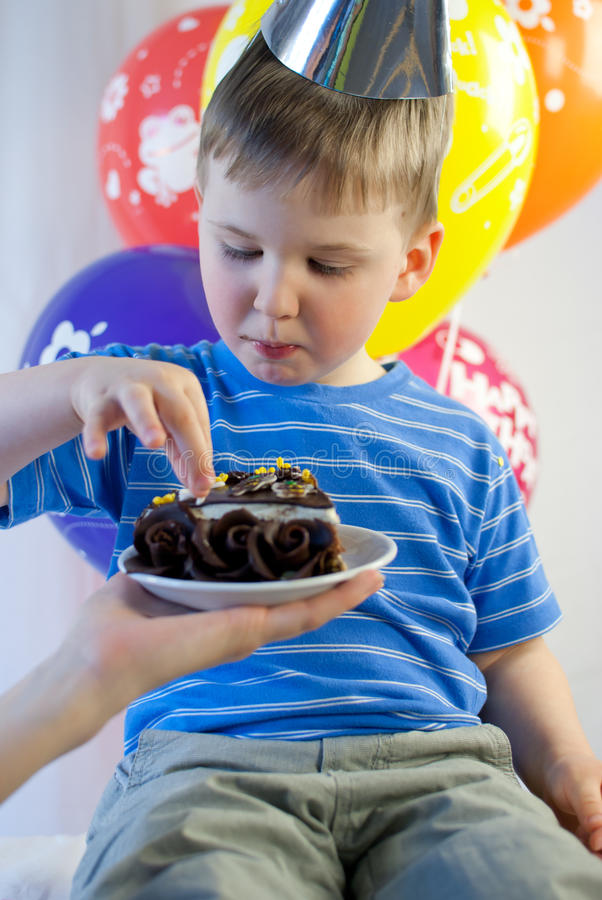 El muchacho feliz come la torta de cumpleaños fotografía de archivo libre de regalías