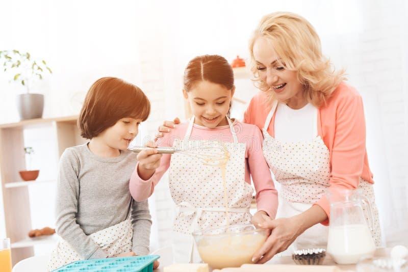 El muchacho feliz con el plato de la hornada mira a la niña que aporrea la pasta en cuenco con su abuela imagen de archivo