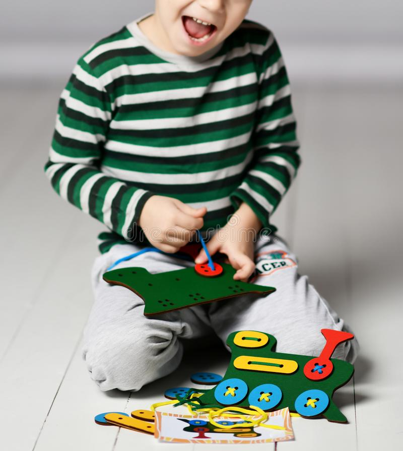 El muchacho feliz del niño juega al juego educativo con el tren y los cordones coloridos de madera imágenes de archivo libres de regalías