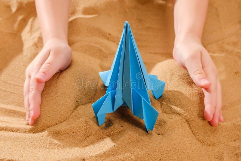El muchacho feliz del niño que juega con la papiroflexia hecha a mano papel, cohete en la arena de la playa, comienza para arriba foto de archivo libre de regalías