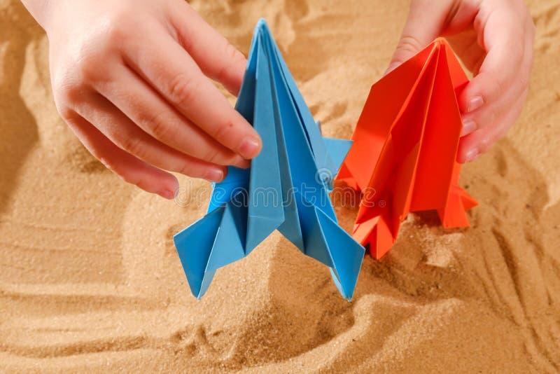El muchacho feliz del ni?o que juega con la papiroflexia hecha a mano papel, cohete en la arena de la playa, comienza para arriba foto de archivo