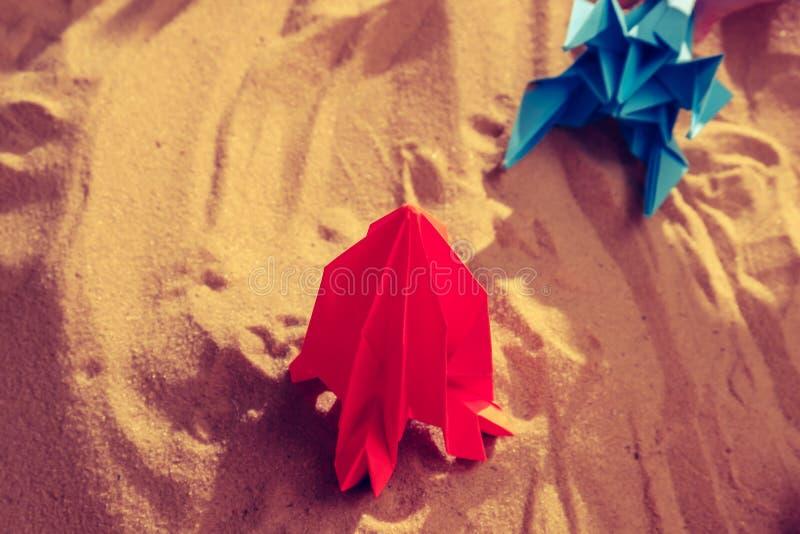 El muchacho feliz del ni?o que juega con la papiroflexia hecha a mano papel, cohete en la arena de la playa, comienza para arriba fotos de archivo