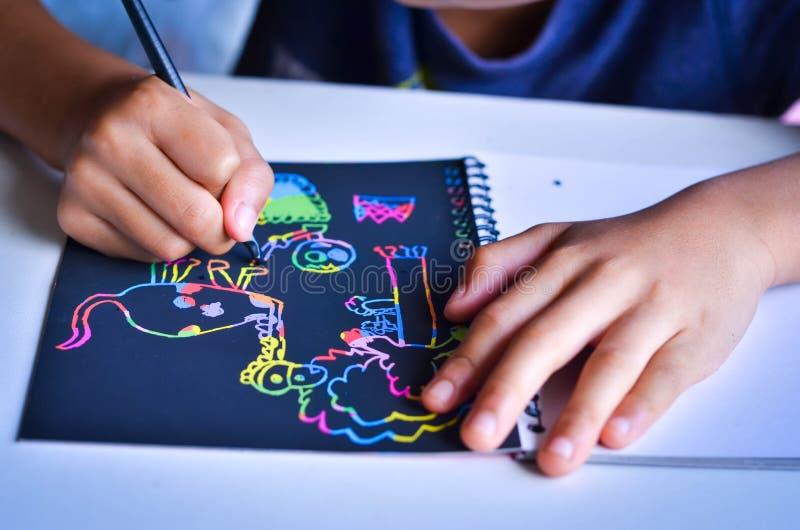El muchacho feliz dibuja en una nota del rasguño colorida fotos de archivo