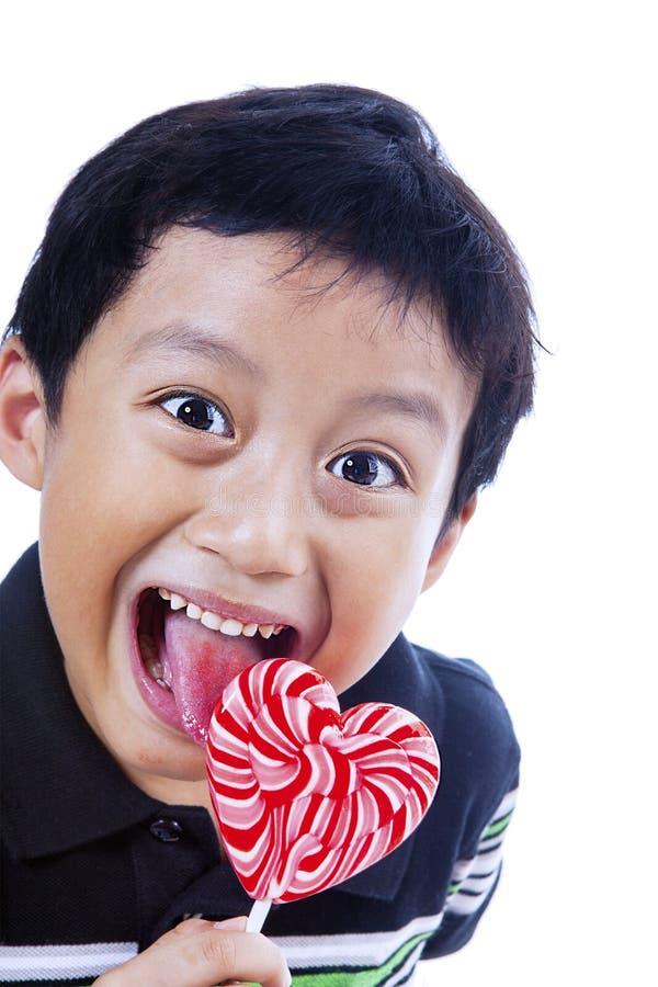 El muchacho feliz quiere el lollipop fotografía de archivo