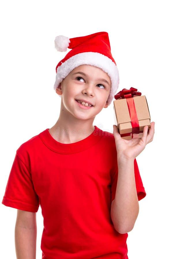 El muchacho feliz, sombrero de santa en su cabeza, recibió la pequeña caja de regalo en la mano Concepto: la Navidad o día de fie foto de archivo libre de regalías