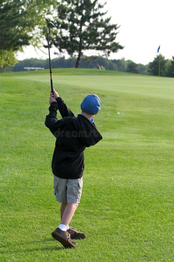 El muchacho golpea la pelota de golf para ponerse verde fotografía de archivo