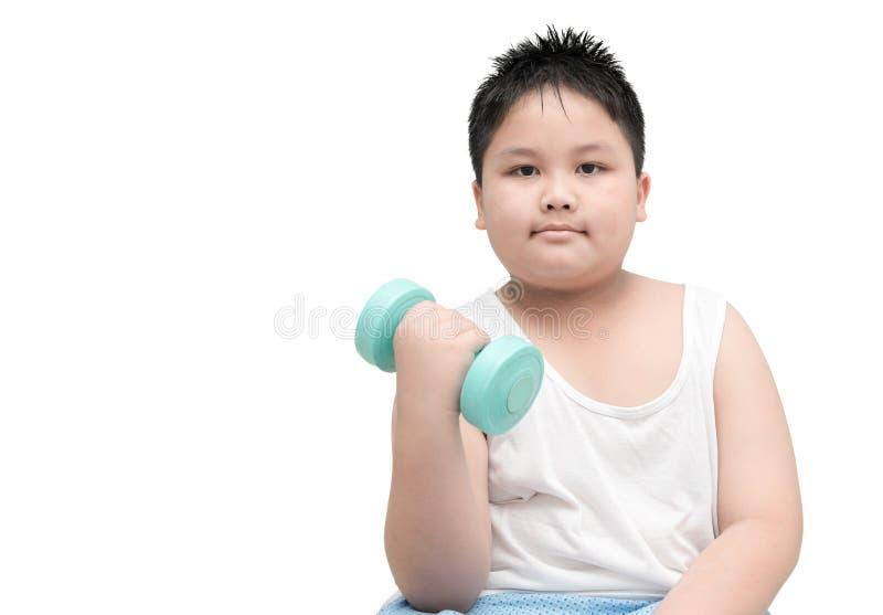 El muchacho gordo obeso está haciendo ejercicios con pesas de gimnasia imagen de archivo