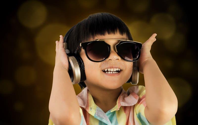 El muchacho goza escucha la música en el auricular con el fondo de oro imagenes de archivo