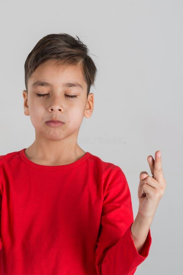 El muchacho ha cerrado ojos y ha cruzado los fingeres en buena suerte o imagen de archivo