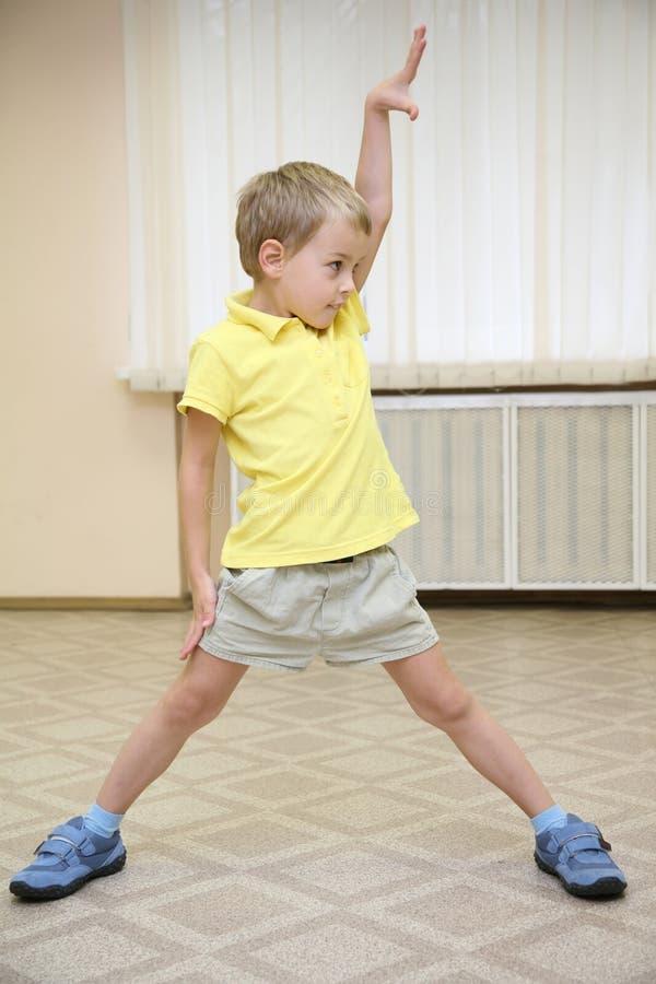 El muchacho hace exercizers imagen de archivo libre de regalías