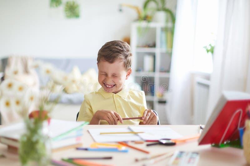 El muchacho hace su preparaci?n en casa el niño feliz en la tabla con sonrisas divertidas de las fuentes de escuela y las arrugas fotografía de archivo libre de regalías