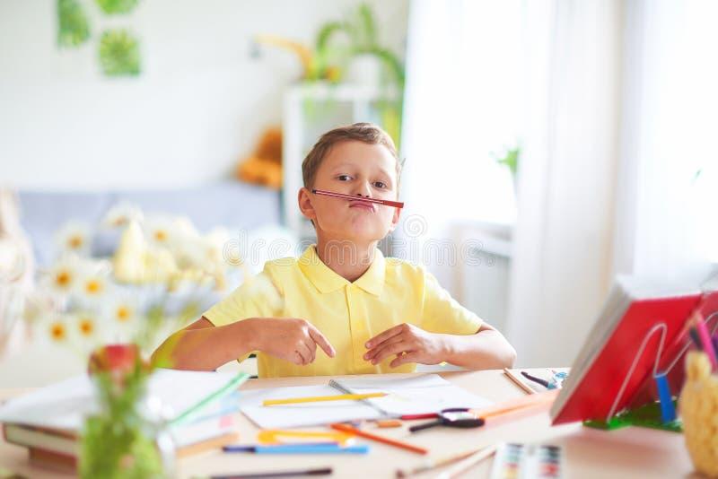 El muchacho hace su preparaci?n en casa el niño feliz en la tabla con sonrisas divertidas de las fuentes de escuela y las arrugas fotos de archivo libres de regalías
