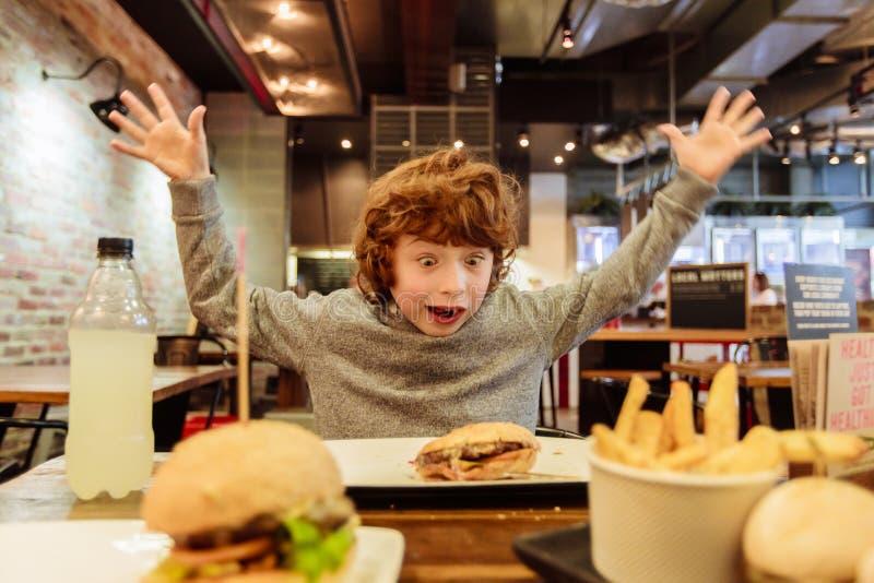 El muchacho hambriento come la hamburguesa en restaurante imagen de archivo