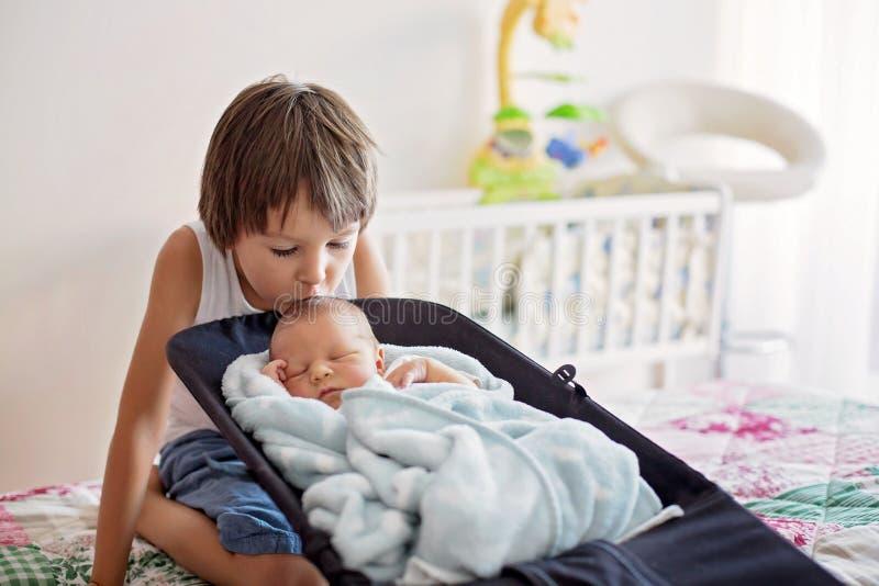 El muchacho hermoso, abrazando con dulzura y cuida a su bebé recién nacido imagen de archivo libre de regalías