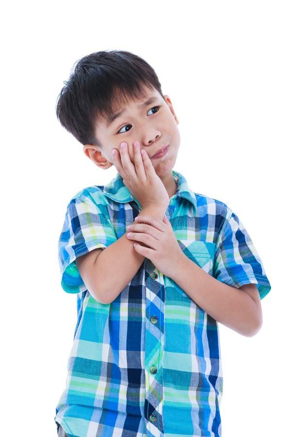 El muchacho hermoso asiático está teniendo dolor de muelas sobre la imagen - una cita del presidente John F foto de archivo