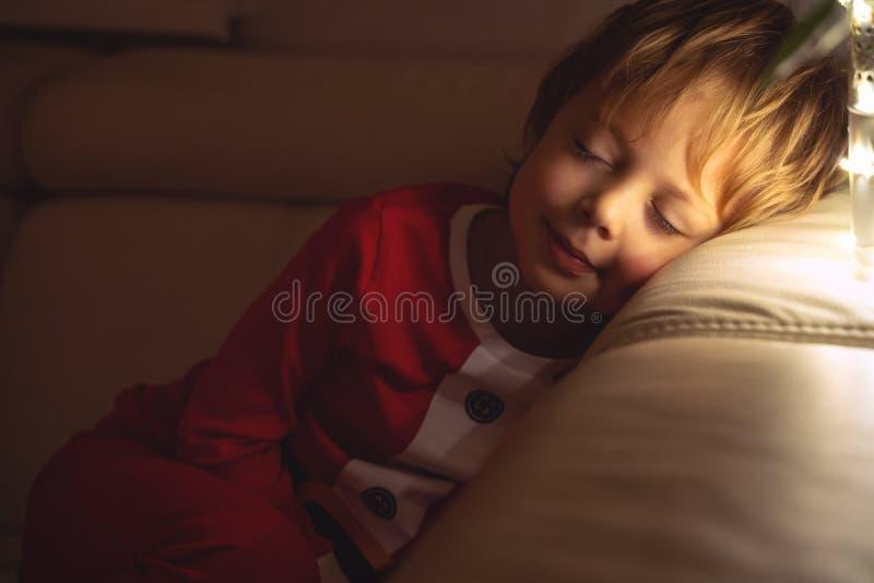 El muchacho hermoso duerme en el sofá en noche de la Navidad Niño que duerme debajo de un árbol de navidad imagen de archivo libre de regalías