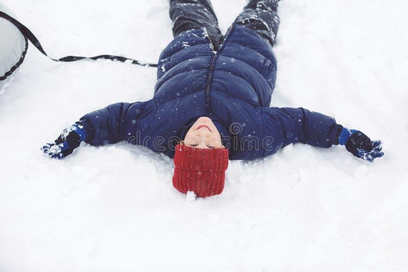 El muchacho hermoso en chaqueta azul, sombrero rojo se divierte en sus vacaciones de invierno Hace el muñeco de nieve, sledding fotografía de archivo libre de regalías