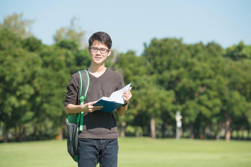 El muchacho hermoso que sostenía un libro abierto, leyó verde del verano del fondo fotografía de archivo libre de regalías
