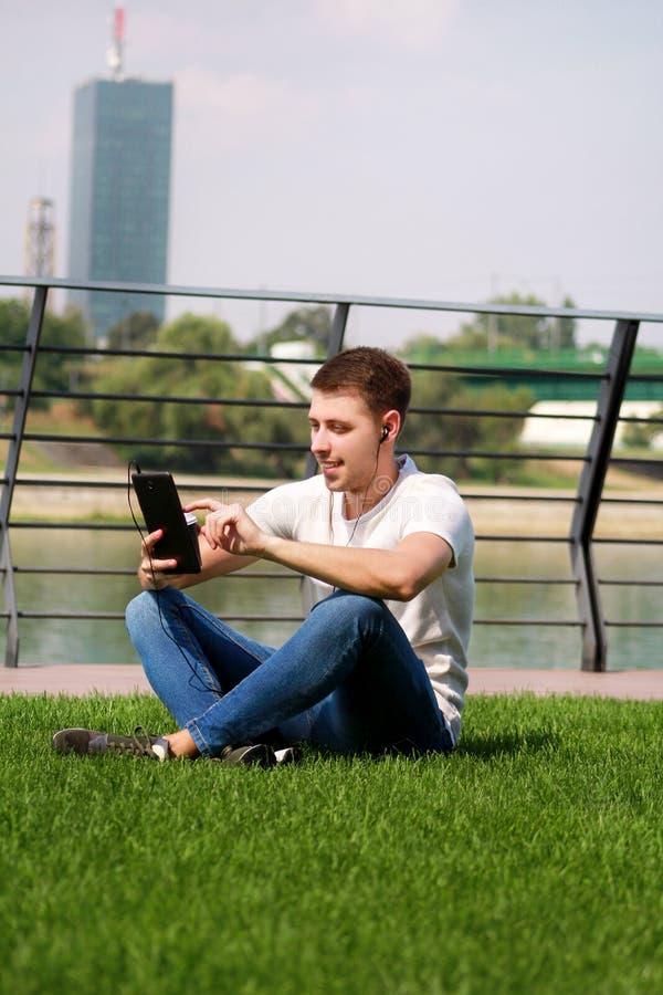 El muchacho hermoso que usa la tableta y los auriculares, café de consumición para ir, sirve sentarse en hierba y disfrutar de dí imagen de archivo libre de regalías