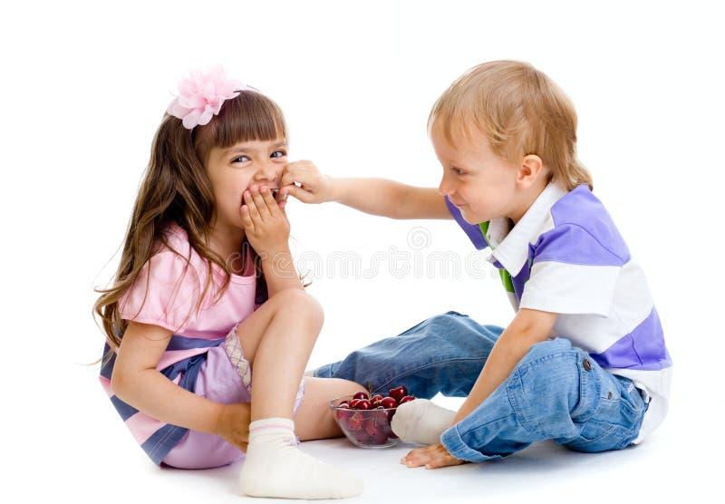El muchacho introduce a la niña con las bayas de la cereza aisladas imágenes de archivo libres de regalías