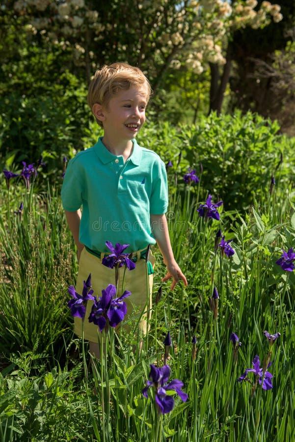 El muchacho joven admira las flores en un jardín al aire libre fotos de archivo