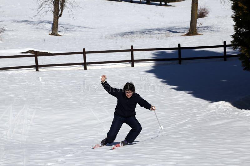 El muchacho joven aprende esquiar en las montañas en invierno imagen de archivo