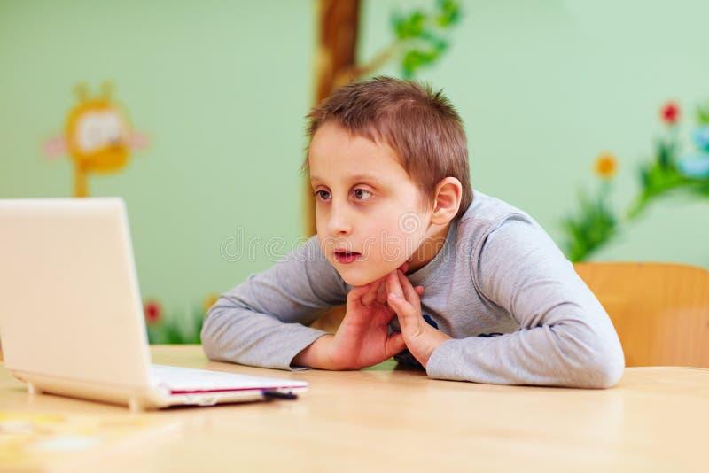 El muchacho joven con el special necesita mirar el vídeo a través del ordenador portátil foto de archivo libre de regalías