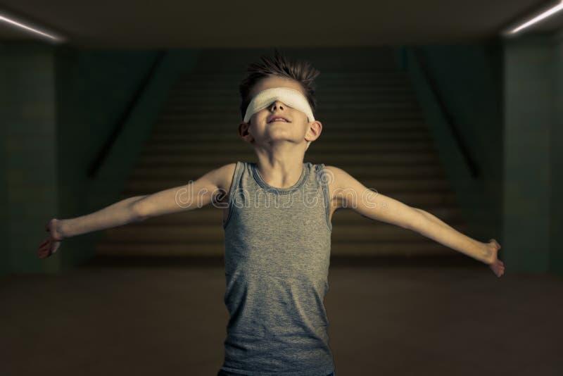 El muchacho joven con los ojos cubrió la apertura de sus brazos de par en par fotos de archivo