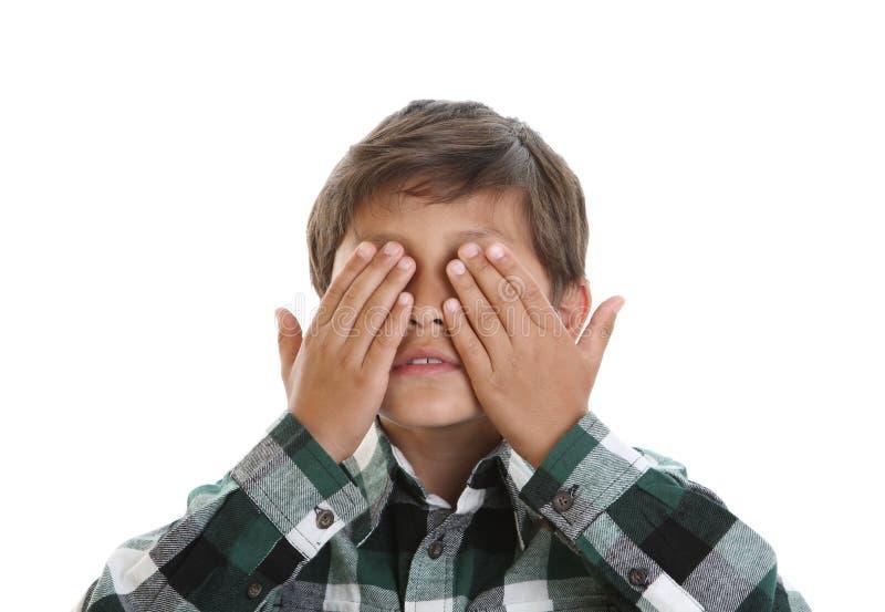 El muchacho joven cubre sus ojos fotografía de archivo libre de regalías