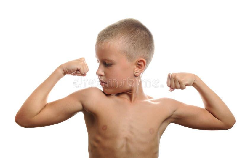 El muchacho joven dobla sus músculos fotos de archivo libres de regalías