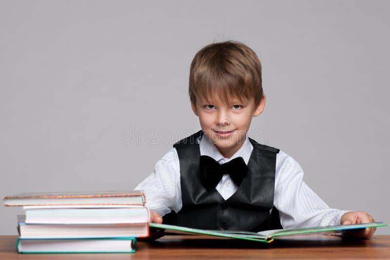 El muchacho joven en el escritorio lee un libro imagen de archivo