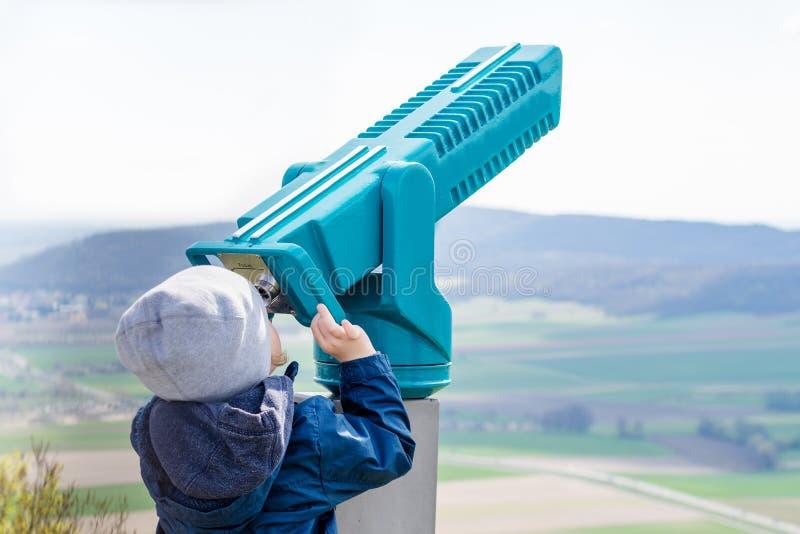 El muchacho joven está mirando a través de un telescopio fotos de archivo libres de regalías