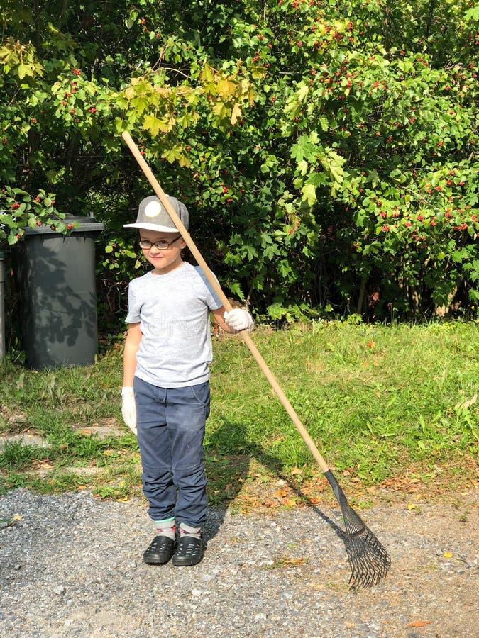 El muchacho joven está rastrillando la basura cerca de su casa Concepto de renovación de la cosecha y del otoño imagen de archivo