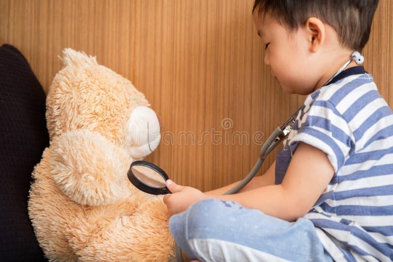 El muchacho joven goza el jugar con el estetoscopio con el juguete, estafa de los niños foto de archivo