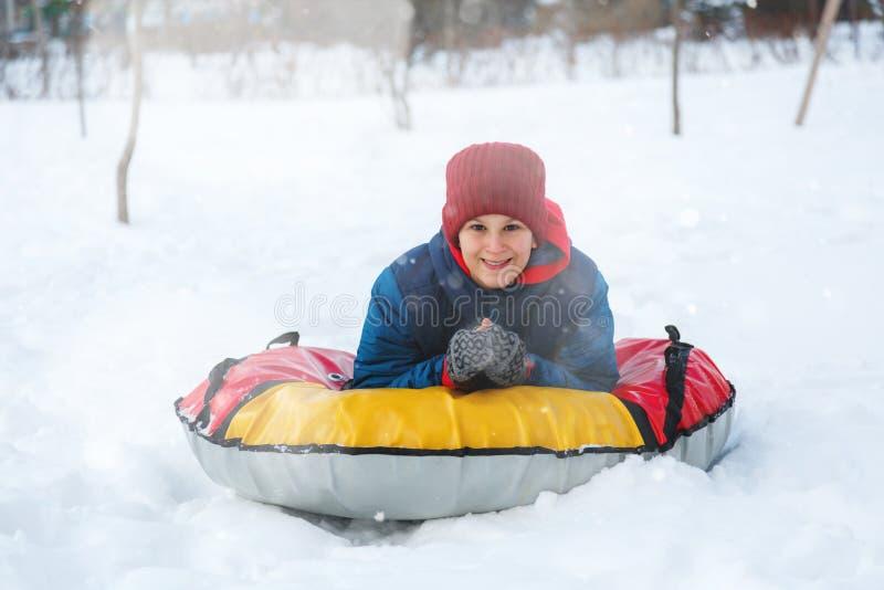 El muchacho joven lindo alegre en bufanda roja del sombrero anaranjado y chaqueta azul sostiene el tubo en nieve, se divierte, so fotografía de archivo