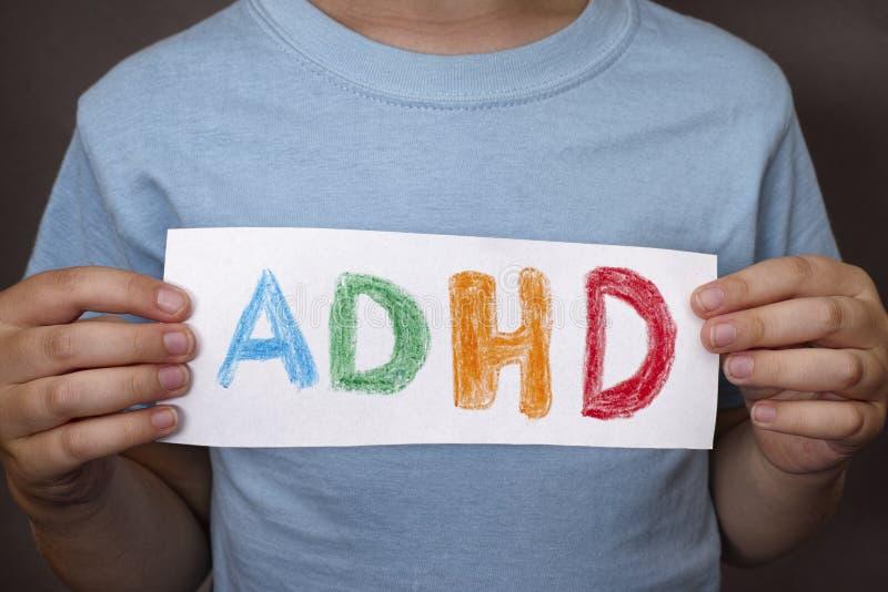 El muchacho joven lleva a cabo el texto de ADHD escrito en la hoja de papel foto de archivo