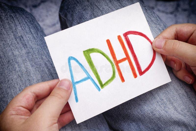 El muchacho joven lleva a cabo el texto de ADHD escrito en la hoja de papel fotos de archivo
