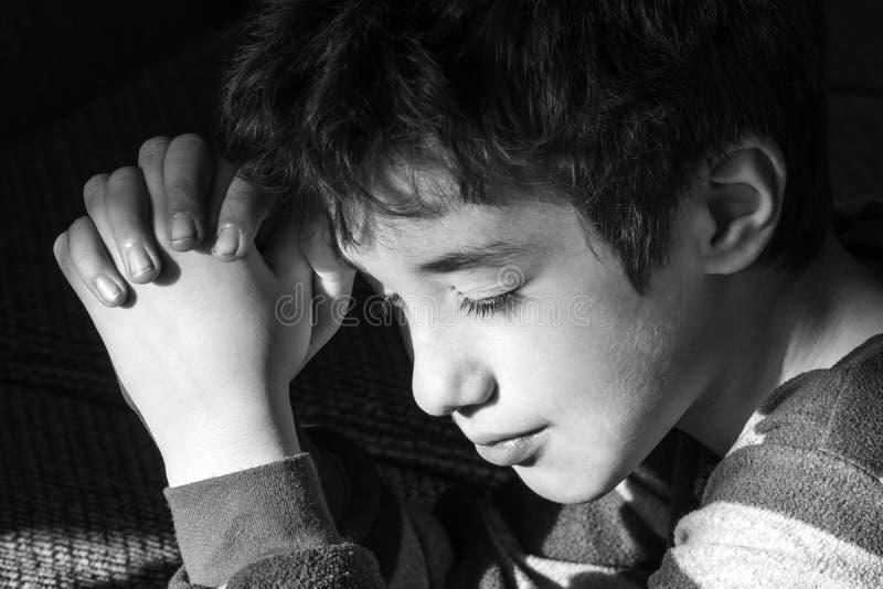 El muchacho joven que sonríe pacífico como él dice rezos de la hora de acostarse, ennegrece a imagen de archivo