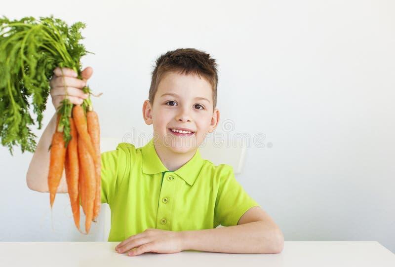 el muchacho joven sostiene una zanahoria fotografía de archivo libre de regalías
