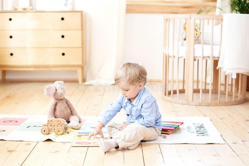 El muchacho juega con los juguetes de madera en casa Juguetes de madera educativos para el niño Retrato de un muchacho que se sie fotografía de archivo libre de regalías