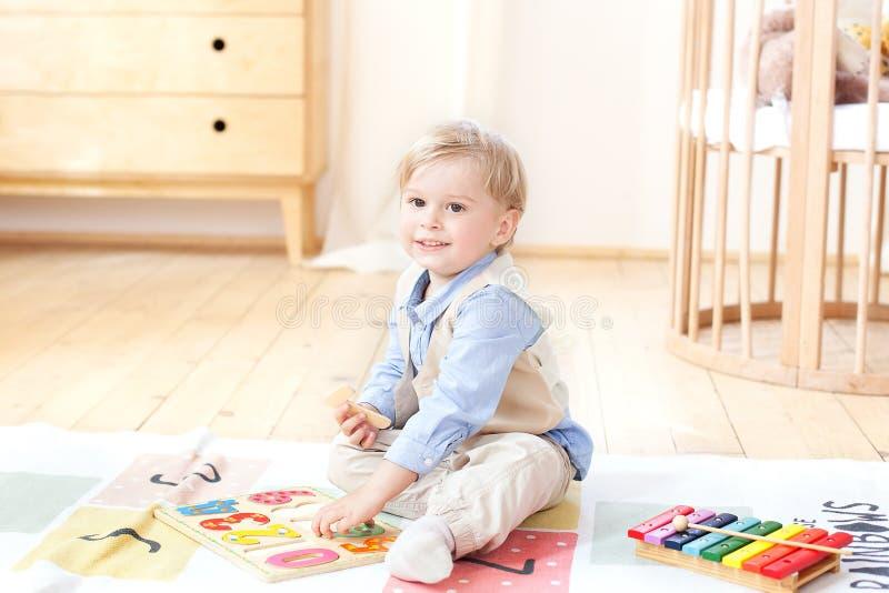 El muchacho juega con los juguetes de madera y los números Juguetes de madera educativos para el niño Retrato de un muchacho que  imagen de archivo libre de regalías
