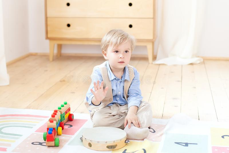 El muchacho juega con un tambor de madera musical y un tren Juguetes de madera educativos para el niño Retrato de un muchacho que imagen de archivo