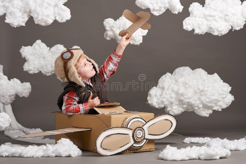 El muchacho juega en un aeroplano hecho de la caja de cartón y de sueños de hacer piloto, nubes de la algodón en un fondo gris fotografía de archivo libre de regalías