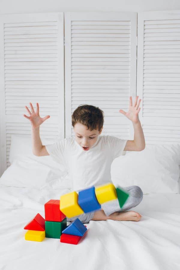 El muchacho juega y construye una torre de cubos plásticos coloridos fotografía de archivo