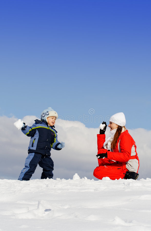 El muchacho jugó con la madre en parque del invierno fotografía de archivo