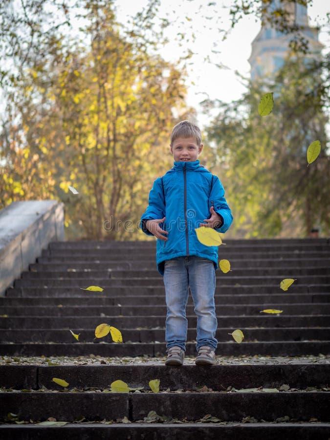 El muchacho lanza las hojas en los pasos en parque del otoño imagenes de archivo